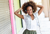 Young black woman, afro hairstyle, in urban street with headphon. Young attractive black woman in urban street listening to the music with headphones. Girl wearing casual clothes with afro hairstyle