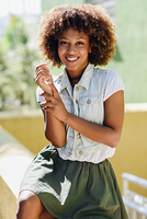 Young black woman, afro hairstyle, smiling in urban background. Young black woman, afro hairstyle, smiling. Girl, model of fashion, wearing casual clothes in urban background. Female with skirt and denim vest.