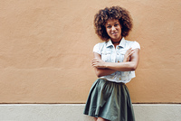 Young black woman, afro hairstyle, smiling in urban background. Young black woman, afro hairstyle, smiling near a wall in the street. Girl wearing casual clothes in urban background.