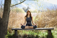 Young beautiful woman doing yoga in nature. Young woman doing yoga in nature. Female wearing sport clothes in lotus figure.