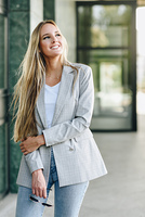Beautiful young blonde woman smiling in urban background.. Beautiful young caucasian woman smiling in urban background. Blond girl wearing casual clothes in the street. Female with elegant jacket and blue jeans