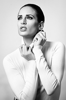 Young brunette woman wearing white poloneck in studio shot. Young brunette woman wearing white poloneck. Attractive girl, model of fashion in black and white. Studio shot on white background.