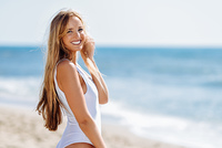 Blond woman with beautiful body in swimswit on a tropical beach. Young blonde woman with beautiful body in white swimsuit on a tropical beach. Caucasian female with straight long hairstyle smiling.