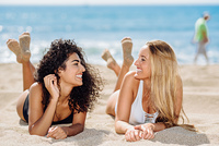 Two young women with beautiful bodies in swimsuit on a tropical . Two young women with beautiful bodies in swimwear on a tropical beach. Funny caucasian and arabic females wearing black and white swimsuits lying on the sand on the beach