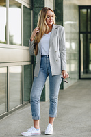 Beautiful young blonde woman in urban background.. Beautiful young caucasian woman in urban background. Blond girl wearing casual clothes in the street. Female with elegant jacket and blue jeans