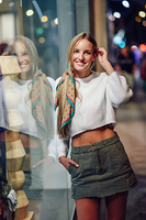 Blonde girl smiling with defocused urban city lights at night. Blonde girl wearing white sweater smiling in the street with defocused city lights at the background. Pretty woman with pigtail hairstyle at night reflected in a shop window.