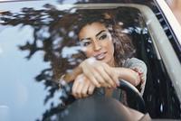 Young arabic woman inside a white car looking through the window. Beautiful young arabic woman inside a nice white car looking through the window. Arab girl wearing casual clothes.