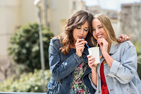 Two young women drinking the same drink with two straws. Two young women drinking the same take away glass together with two straws outdoors.