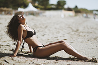 Arabic woman with beautiful body in bikini lying on the beach sa. Young arabic woman with beautiful body in swimwear lying on the beach sand. Smiling female with curly long hairstyle wearing black bikini.