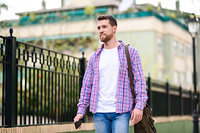 Young bearded man walking in urban background. Lifestyle concept. Young bearded man walking in urban background. Traveler wearing casual clothes. Lifestyle concept.