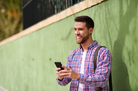 Young man laughing with his smart phone in urban background. Lif. Young man laughing with his smart phone in urban background. Guy wearing casual clothes. Lifestyle concept.