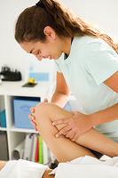 Medical massage at the leg in a physiotherapy center.. Medical massage at the leg in a physiotherapy center. Female physiotherapist inspecting her patient.
