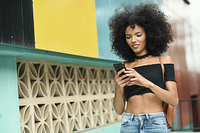 Black woman afro hair on the street holding a smartphone. Young black woman with afro hair walking on the street holding a smart phone. Female wearing casual clothes in urban background. Lifestyle concept
