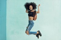 Young mixed woman with afro hair jumping outdoors.. Young mixed woman with afro hair jumping outdoors. Female wearing casual clothes in urban background. Lifestyle concept