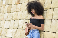 Serious black woman looking at her smart phone outdoors. Serious black woman with afro hair looking at her smart phone outdoors. Lifestyle concept
