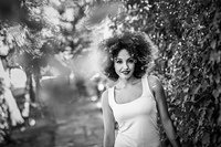 Young black woman with afro hairstyle smiling in urban park. Young black woman with afro hairstyle smiling in urban park. Mixed girl wearing casual clothes. Black and white photograph.