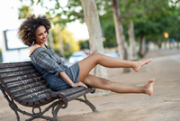Young black woman with afro hairstyle smiling in urban backgroun. Young black woman with afro hairstyle sitting on a bench in urban background moving her legs. Mixed girl wearing casual clothes.