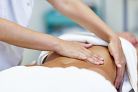 Woman having abdomen massage by professional osteopathy therapis. Female patient is receiving treatment by professional osteopathy therapist. Woman having abdomen massage in a physiotherapy center.