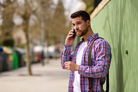 Young man talking with his smart phone in urban background. Life. Young man talking with his smart phone in urban background. Guy wearing casual clothes. Lifestyle concept.