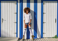 Young black woman on roller skates near a beach hut. Girl with afro hairstyle rollerblading on sunny promenade.. Young black woman on roller skates near a beach hut.