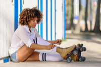 Young black woman sitting on wooden floor puts on skates. Girl with afro hairstyle wearing white sports clothes near the beach.. Young black woman sitting on wooden floor puts on skates.