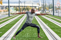 Black man practicing yoga in urban background. Black man practicing yoga in urban background. African male doing workout outdoors.