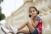 Adorable little girl combed with pigtails outdoors sitting on urban floor.