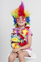 Funny beautiful party little girl in disguise with wig in many colors and pink round sunglasses