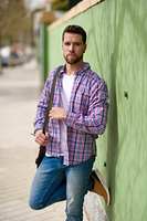 Attractive young man standing in urban background. Guy wearing casual clothes. Lifestyle concept.