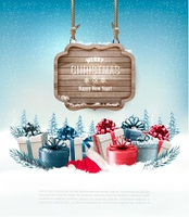 Winter background with gift boxes and a wooden ornate Merry christmas sign