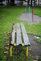 秋の公園の朽ちたベンチ