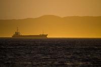遠く朝日に光る波の上を進む船