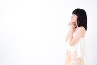 横を向いて祈るポーズをする女性