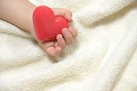 ハートのおもちゃを持つ赤ちゃんの手