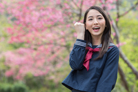 桜の前でガッツポーズをとる女学生