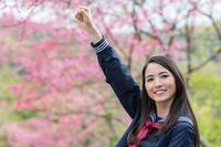 桜の前で拳をあげる女学生