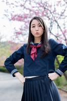 桜の前で腰に手をあてる女学生