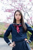 桜の前で腰に手を当てて怒る女学生