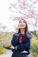 桜の前で空を指差す若い女性