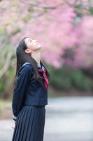 桜の前で空を見上げる若い女性