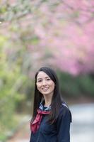 桜の前で笑顔の若い女性