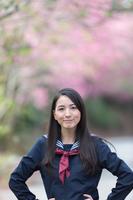 桜の前で腰に手をあてる若い女性