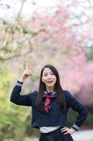 桜の前で上を指差す女学生