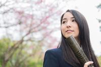 桜の前で証書筒を持つ女学生