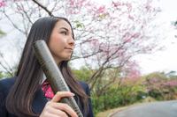 桜の前で賞状筒を持つ女学生