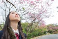 証書筒を持って空を見上げる女学生
