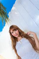白い壁の前に立つ若い女性