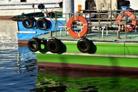 晴れた港に停泊している青色と緑色の船
