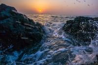 朝日を背に磯に打ち寄せる波1