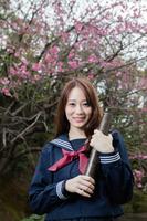桜の木の前で証書筒を手にする女学生